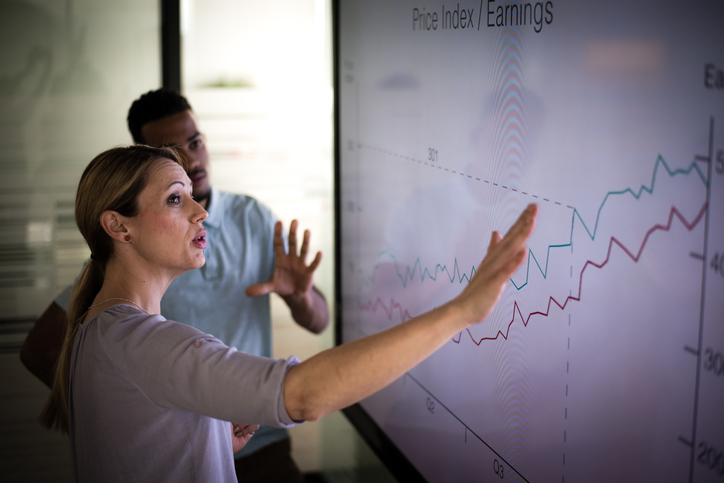 Businesswoman explaining graph to his coworker in conference room.
